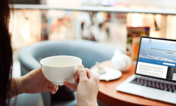 Woman drinking coffee and looking at her laptop